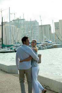 海沿いを笑顔で歩くカップルの写真素材 [FYI03955031]