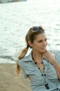 海沿いに座ってリラックスする女性の写真素材 [FYI03955038]