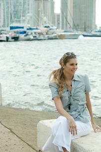 海沿いに座ってリラックスする女性の写真素材 [FYI03955041]