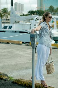 パーキングメーターの横に立つ女性の写真素材 [FYI03955054]