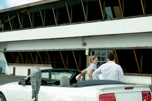 オープンカーに寄りかかって話すカップルの写真素材 [FYI03955055]