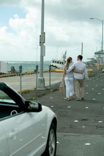 海沿いの駐車場を歩くカップルの写真素材 [FYI03955057]