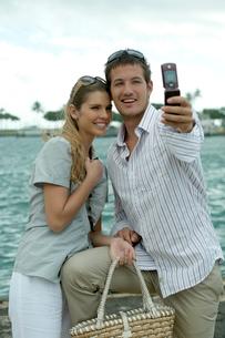 海沿いで記念撮影をするカップルの写真素材 [FYI03955061]