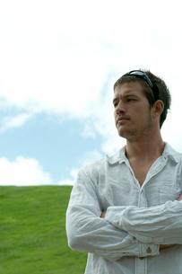 芝生の上に立って遠くを眺める男性の写真素材 [FYI03955063]