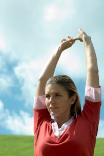 芝生の上でストレッチをする女性の写真素材 [FYI03955065]