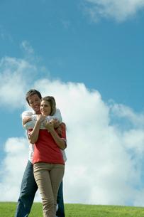芝生の上で女性を抱きしめる男性の写真素材 [FYI03955080]