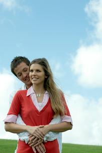 芝生の上で女性を抱きしめる男性の写真素材 [FYI03955081]