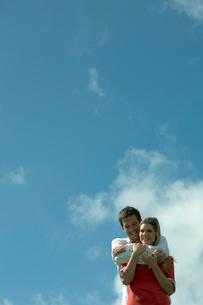 青空の下で女性を抱きしめる男性の写真素材 [FYI03955082]