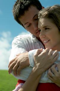 芝生の上で女性を抱きしめる男性の写真素材 [FYI03955083]
