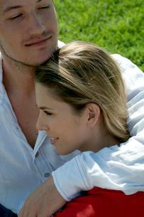 芝生の上に座って女性を抱き寄せる男性の写真素材 [FYI03955088]
