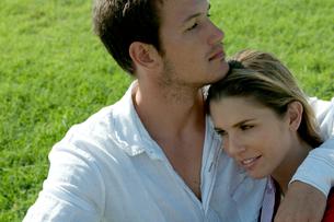 芝生の上に座って女性を抱き寄せる男性の写真素材 [FYI03955089]