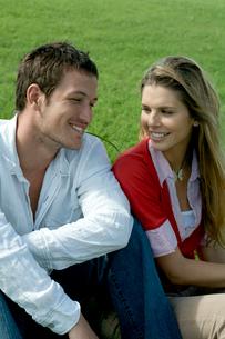 芝生の上に座って会話をするカップルの写真素材 [FYI03955092]