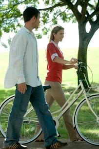 公園で自転車を引く女性と側を歩く男性の写真素材 [FYI03955099]