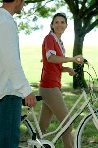 公園で自転車を引く女性と側を歩く男性の写真素材 [FYI03955100]