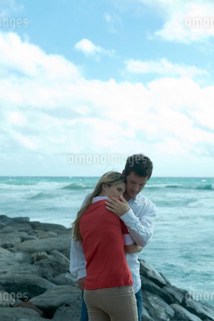 海沿いの岩場で女性を抱きしめる男性の写真素材 [FYI03955108]