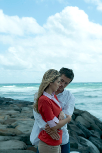 海沿いの岩場で女性を抱きしめる男性の写真素材 [FYI03955109]