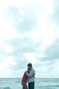 海沿いの岩場で女性を抱きしめる男性の写真素材 [FYI03955110]