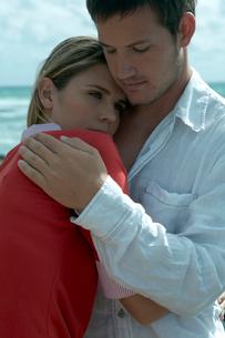 海沿いの岩場で女性を抱きしめる男性の写真素材 [FYI03955111]