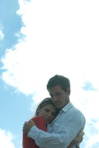 海沿いの岩場で女性を抱きしめる男性の写真素材 [FYI03955112]