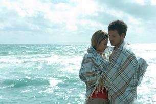 海沿いで毛布を被って抱き合うカップルの写真素材 [FYI03955113]