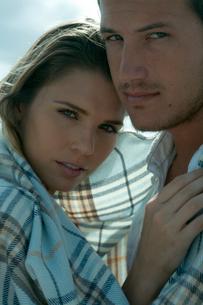 海沿いで毛布を被って抱き合うカップルの写真素材 [FYI03955115]