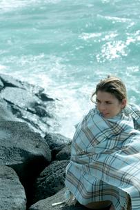 海沿いの岩場で毛布を被って座る女性の写真素材 [FYI03955117]