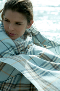 海沿いの岩場で毛布を被って座る女性の写真素材 [FYI03955118]