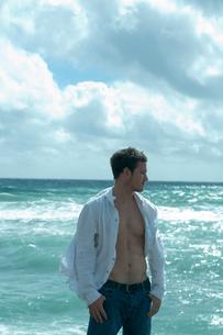 海沿いの岩場に立つ男性の写真素材 [FYI03955119]