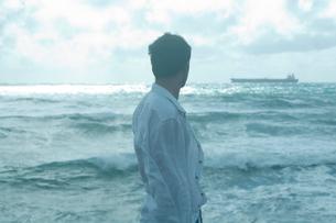 海沿いで遠くの船を眺める男性の写真素材 [FYI03955120]