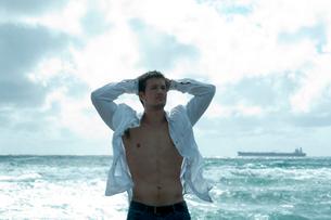 海沿いでリラックスする男性の写真素材 [FYI03955121]