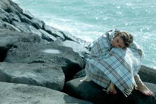 海沿いの岩場で毛布を被って座る女性の写真素材 [FYI03955122]