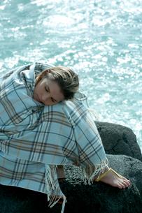海沿いの岩場で毛布を被って座る女性の写真素材 [FYI03955123]