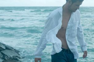 海沿いの岩場に立つ男性の写真素材 [FYI03955124]
