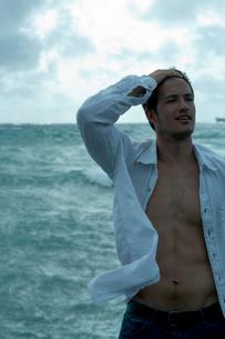 海沿いでリラックスする男性の写真素材 [FYI03955128]