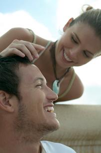 男性の頭を撫でる女性の写真素材 [FYI03955140]