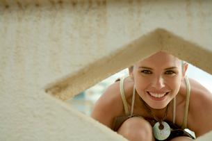 壁の穴から覗き込む女性の写真素材 [FYI03955143]