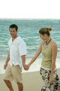 海岸で手を繋いで散歩するカップルの写真素材 [FYI03955144]
