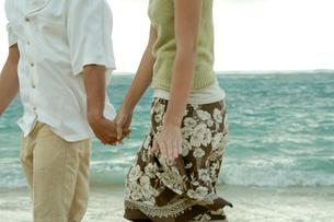 海岸で手を繋いで散歩するカップルの写真素材 [FYI03955146]