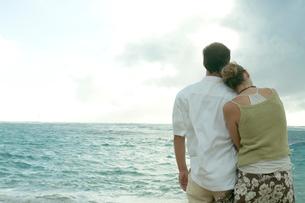 海岸で夕日を眺めるカップルの写真素材 [FYI03955153]