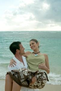 海岸で女性を抱きかかえる男性の写真素材 [FYI03955154]