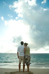 海岸で夕日を眺めるカップルの写真素材 [FYI03955155]