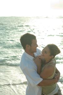 夕暮れの海岸で寄りそうカップルの写真素材 [FYI03955167]