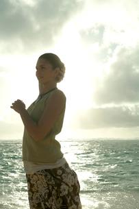 夕暮れの海岸でリラックスする女性の写真素材 [FYI03955168]