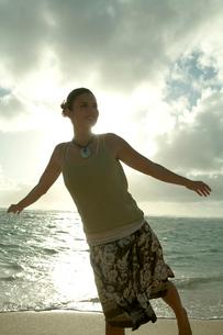 夕暮れの海岸でリラックスする女性の写真素材 [FYI03955169]
