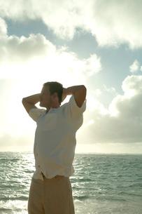 夕暮れの海岸でストレッチをする男性の写真素材 [FYI03955170]