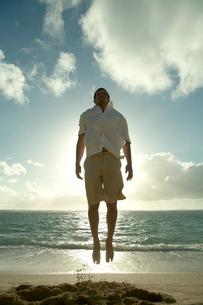 夕暮れの海岸でジャンプをする男性の写真素材 [FYI03955171]