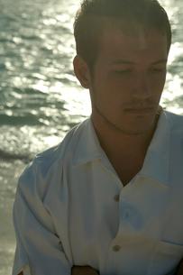 夕暮れの海岸でたそがれる男性の写真素材 [FYI03955173]