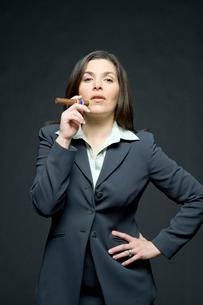 片手を腰にあて葉巻を吸うビジネスウーマンの写真素材 [FYI03955180]