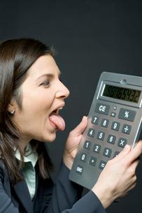 電卓の数字を見て舌を出して喜ぶビジネスウーマンの写真素材 [FYI03955186]