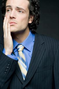 片手を頬にあてて悩むビジネスマンの写真素材 [FYI03955192]